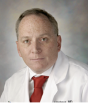 Headshot of Dr. McManus wearing white coat and red tie.